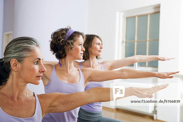 Drei Frauen machen Yoga in einem Fitnessstudio