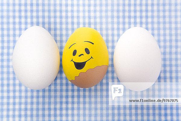 Ei mit Smiley-Gesicht zwischen zwei weißen Eiern