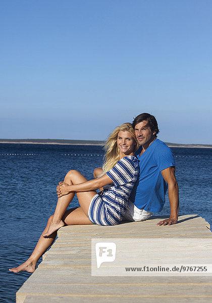 Lächelndes Paar sitzt auf einem Steg