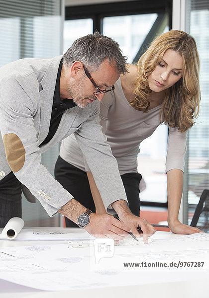 Geschäftsmann und Geschäftsfrau schauen auf Bauplan