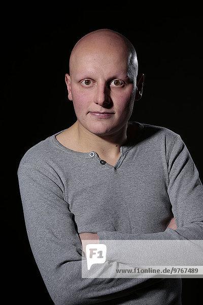 Ernster junger Mann mit Glatze  Porträt