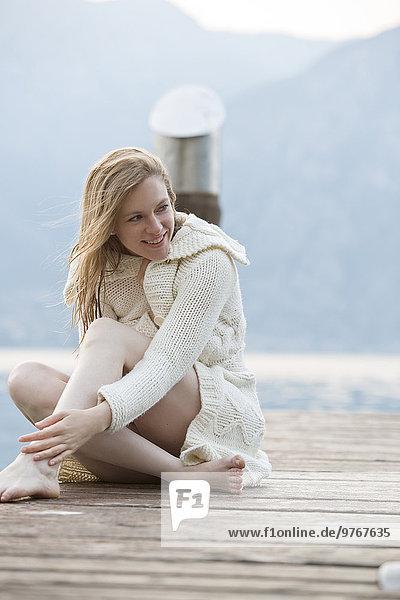 Frau sitzt auf einem Steg am Gardasee  Italien
