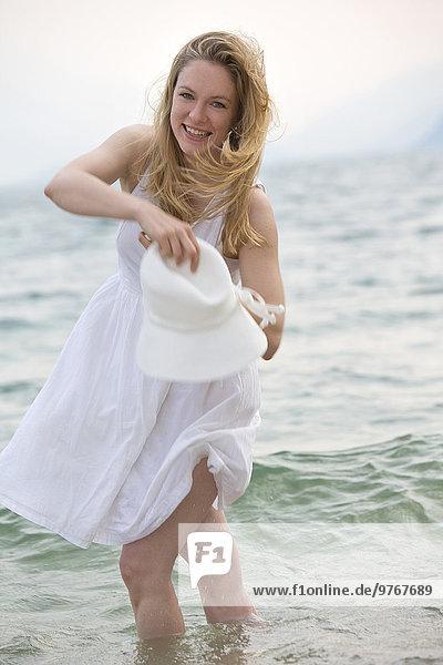 Happy woman in white dress in Lake Garda  Italy
