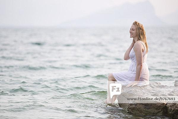 Fröhliche Frau in weißem Kleid am Gardasee  Italien