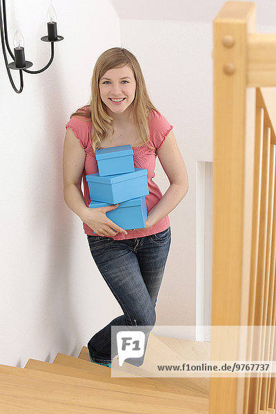 Smiling woman with boxes on stairs