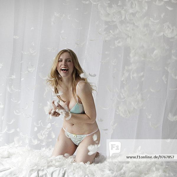Fröhliche Frau in Unterwäsche im Bett umgeben von Federn