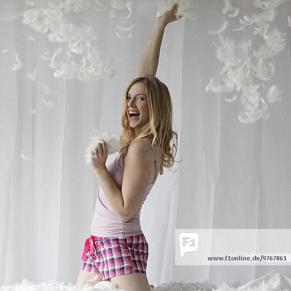 Fröhliche Frau im Bett umgeben von Federn