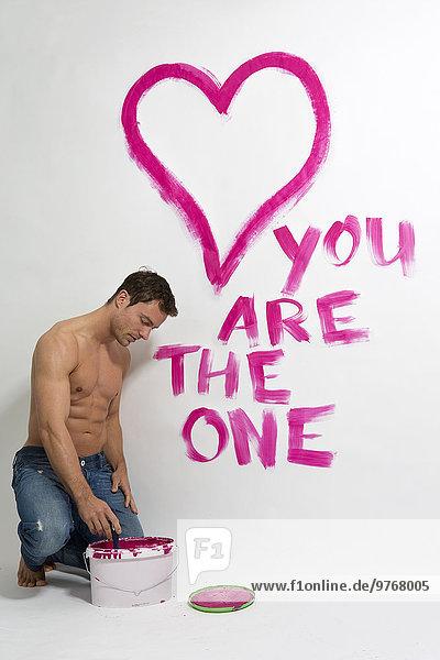 Attraktiver Mann mit freiem Oberkörper malt ein Herz und Wörter an die Wand
