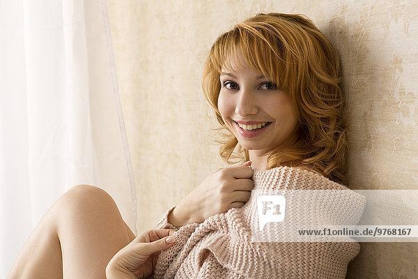 Lächelnde junge Frau mit Strickjacke