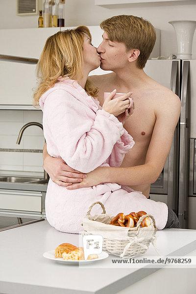 Junges Paar in der Küche umarmt und küsst sich am Morgen