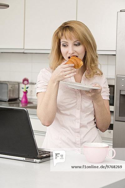 Junge Frau benutzt einen Laptop in der Küche