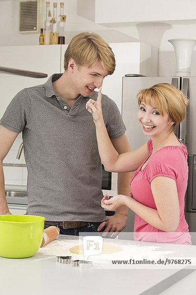 Verspieltes junges Paar in der Küche