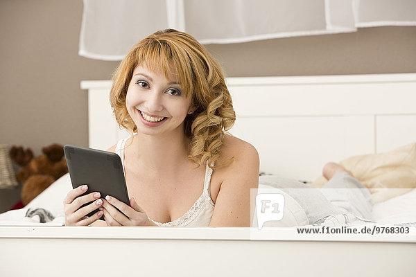 Junge Frau liegt mit einem E-Book im Bett