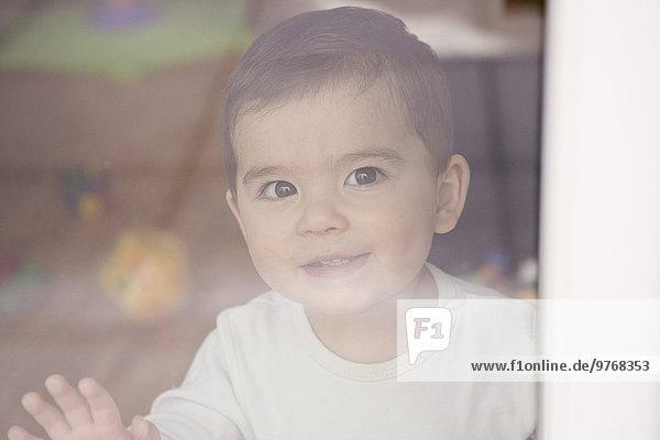 Fröhlicher kleiner Junge hinter einer Fensterscheibe