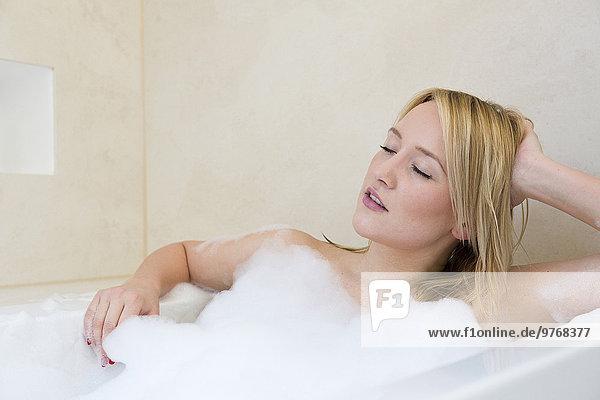 Blonde junge Frau genießt ein Bad in der Wanne
