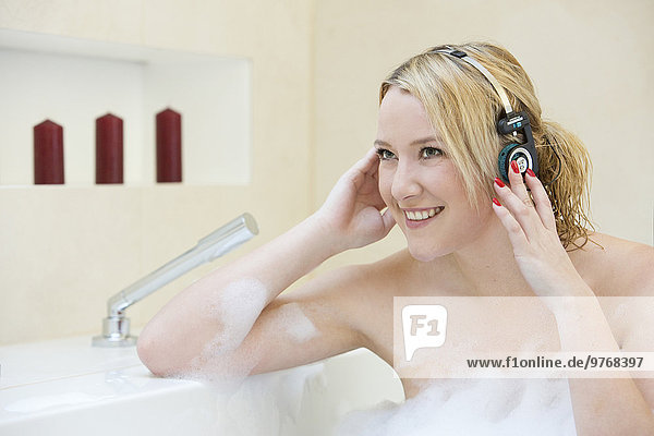 Blonde junge Frau mit Kopfhörern in der Badewanne