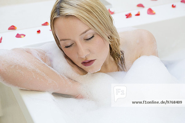 Blonde junge Frau genießt ein Bad in der Wanne mit Rosenblütenblättern