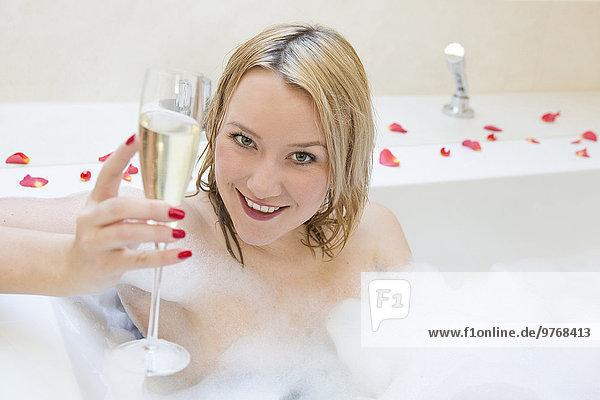 Blonde junge Frau mit einem Glas Sekt in der Badewanne