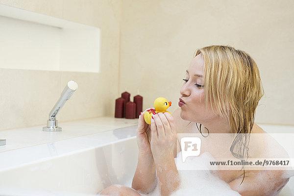 Blonde junge Frau mit Gummiente in der Badewanne