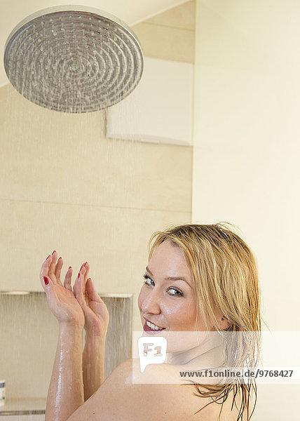 Blonde junge Frau in der Dusche
