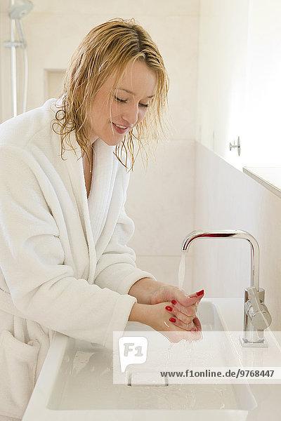 Blonde junge Frau im Bademantel wäscht sich die Hände