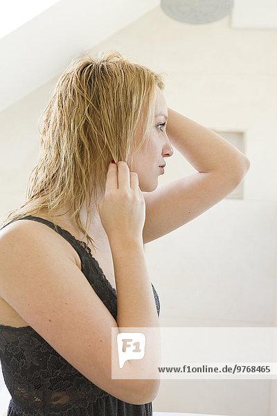 Blonde junge Frau im Negligé im Badezimmer