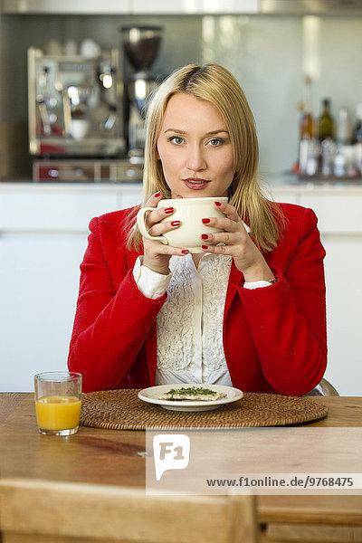 Blonde junge Frau in der Küche mit einer Tasse Kaffee