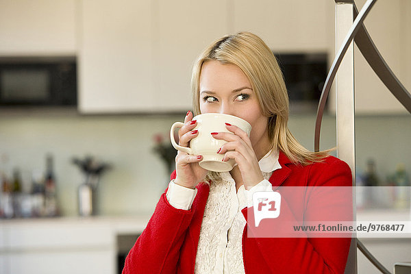 Blond young woman in kitchen holding cup of coffee
