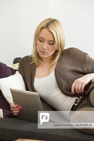 Blonde junge Frau im Wohnzimmer benutzt einen Tablet-Computer