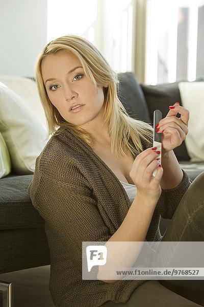 Blonde junge Frau im Wohnzimmer bei der Maniküre