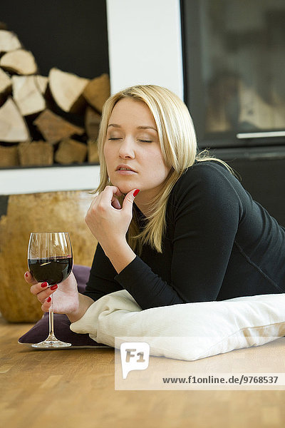 Blond young woman lying at the fireplace with glass of red wine