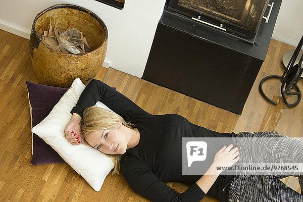 Blonde junge Frau liegt auf dem Boden