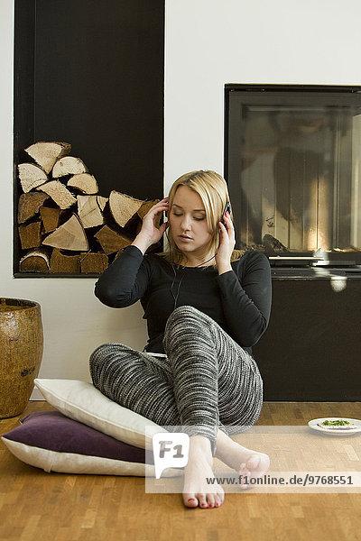Blonde junge Frau sitzt am Kamin und hört Musik