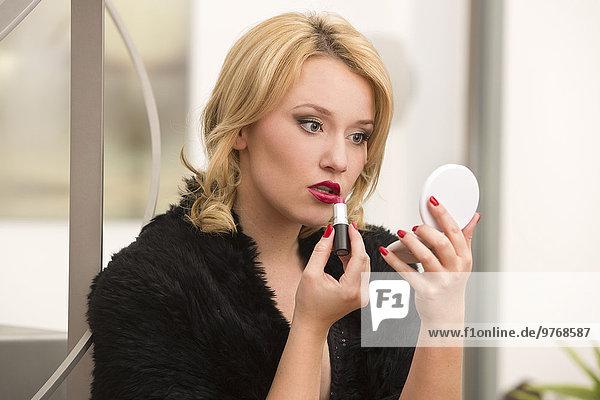 Junge Frau in Abendgarderobe trägt Lippenstift auf
