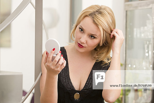 Junge Frau in Abendgarderobe hält einen Kosmetikspiegel