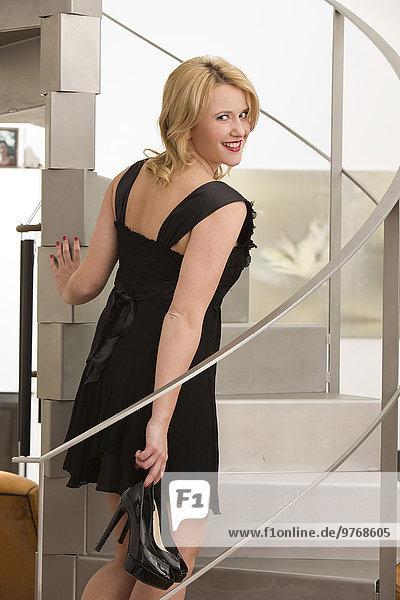 Lächelnde junge Frau im Abendkleid auf einer Treppe