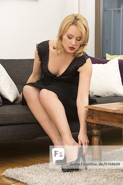 Junge Frau auf einer Couch zieht High Heels an