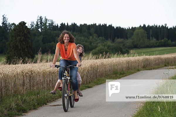 Mutter und Tochter mit Fahrrad auf einem Feldweg