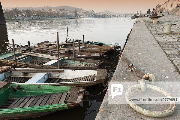 Fishing boats  ducks  Vltava River and Prague Castle during autumn at embankment below Rasinovo nabrezi  Vyton  Nove Mesto  Prague  Czech Republic  Europe