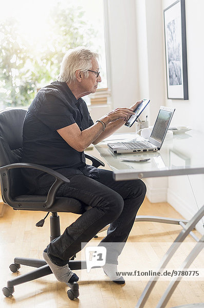 Senior man sitting in home office  using tablet pc