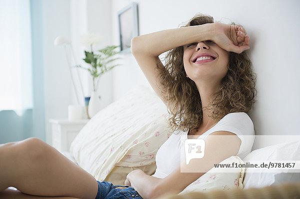 sitzend junge Frau junge Frauen lächeln Bett bedecken