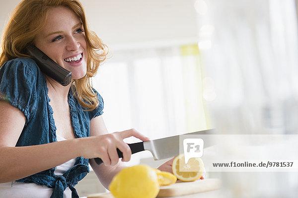 junge Frau junge Frauen sprechen schneiden Zitrusfrucht Zitrone telefoniert