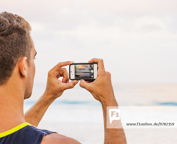Young man taking photo of sea