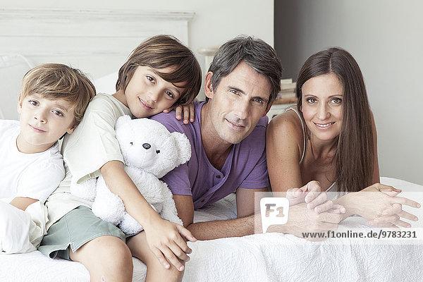 Eltern und kleine Söhne entspannen sich gemeinsam auf dem Bett  Porträt