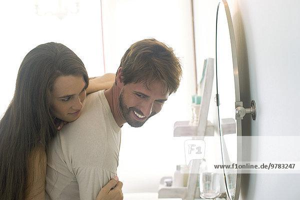 Frau umarmt Mann von hinten