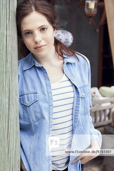 Junge Frau an Holzpfosten gelehnt  Porträt