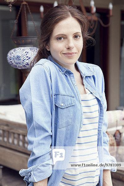 Junge Frau im Freien mit Händen in den Taschen  lächelnd  Portrait
