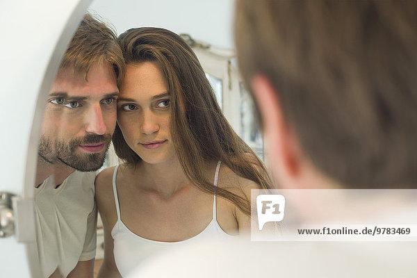 Paar Wange an Wange zusammen in den Spiegel schauen