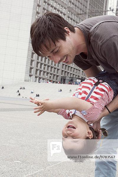 Vater hält jungen Sohn kopfüber  beide lachend