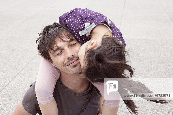 Ein kleines Mädchen  das auf Vaters Schultern reitet und seine Wange küsst.